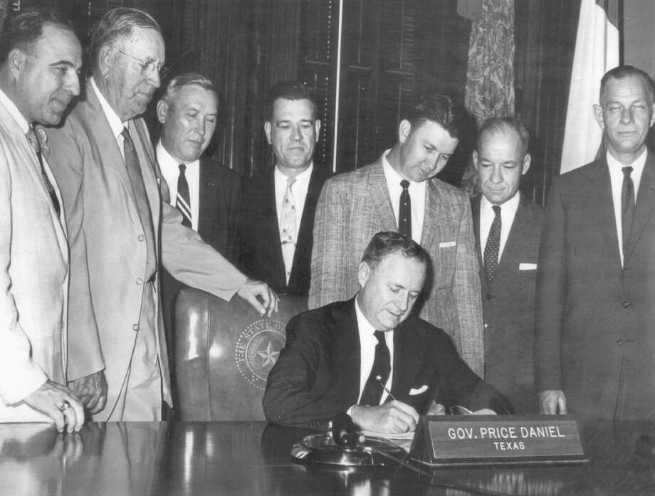 Texas Gov. Price Daniel, seated, signed a bill on April 29, 1959 establishing the South Texas Medical School in San Antonio. In 1972, the school was renamed the University of Texas Health Science Center at San Antonio. Standing left to right are Sen. Henry B. Gonzalez, Sen. R.A. Weinert, Dr. James Hollers, Dr. John Smith Jr., Rep. R.L. Strickland, Dr. John Matthews and Dr. L. Bonham Jones. Photo: Courtesy UT Health Science Center At San Antonio