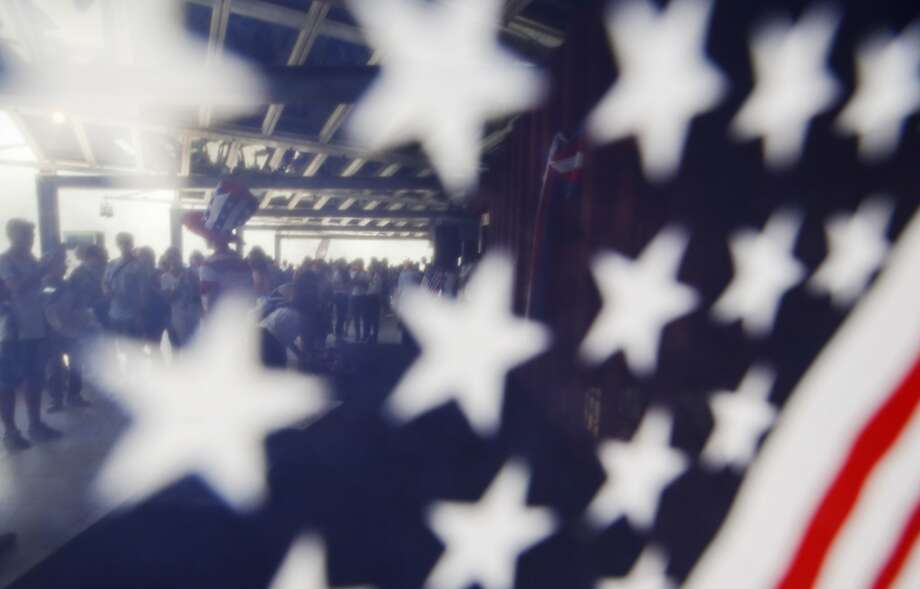 People gathered on the roof of the US pavilion are seen through a USA flag as they take part at the official opening of the National Day USA, at the Expo 2015 world's fair in Rho, near Milan, Italy, Saturday, July 4, 2015. (AP Photo/Luca Bruno) Photo: Luca Bruno, Associated Press