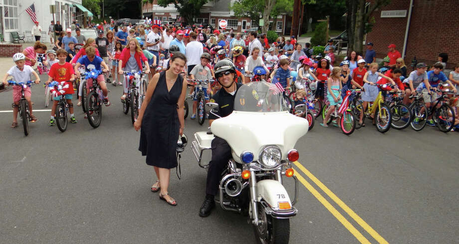 Pequot Library Executive Director Heather-Marie Montilla and Motorcycle Police Officer Chris Mastronardi at the start of the library's July 4 Bike Parade on Saturday morning. Photo: Mike Lauterborn / For Hearst Connecticut Media / Fairfield Citizen