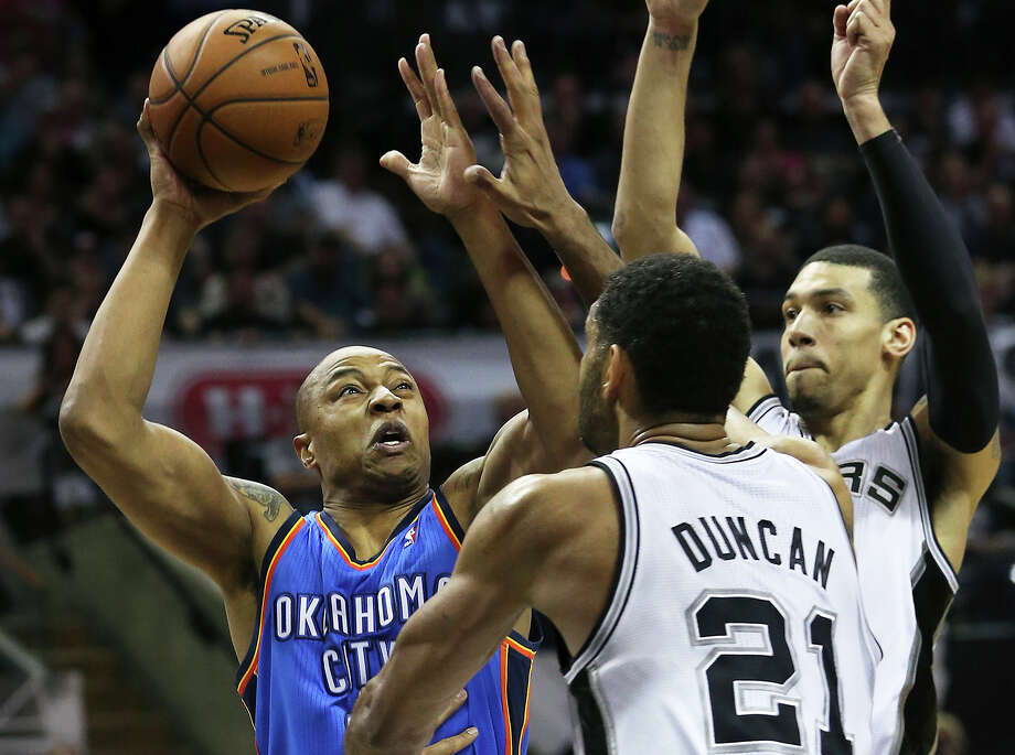 Caron Butler tries a shot underneath against Tim Duncan as the San Antonio Spurs play the Oklahoma City Thunder in game 2 of the Western Conference Finals at the AT&T Center on May 21, 2014. Photo: TOM REEL