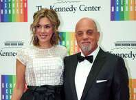 FILE - In this Dec. 7, 2013 file photo, Kennedy Center Honoree Billy Joel,right, and Alexis Roderick arrive at the Kennedy Center Honors gala dinner in Washington. Joel married girlfriend Alexis Roderick in a surprise ceremony at the couple's annual July 4 party. The singer's spokeswoman Claire Mercuri says New York Gov. Andre Cuomo presided over Saturday's nuptials at Joel's Long Island estate. (AP Photo/Kevin Wolf, File) ORG XMIT: NYET602