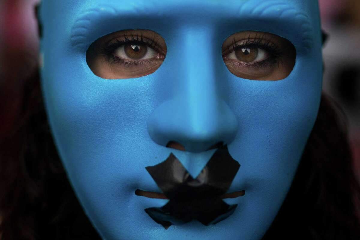 A protestor wears a mask with a gag as she marches against the Public Security Law in Madrid, Spain, Tuesday, June 30, 2015. Thousands of protesters railed Tuesday against a new Spanish public security law nicknamed the