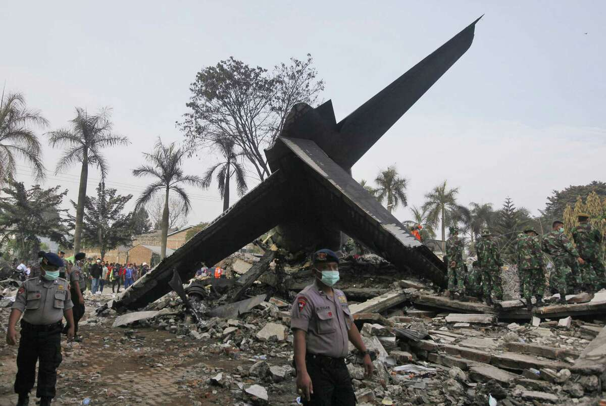 Rescuers search for victims at the site where an Indonesian air force transport plane crashed in Medan, North Sumatra, Indonesia, Wednesday, July 1, 2015. The C-130 Hercules plane crashed into a residential neighborhood in the country's third-largest city on June 30.
