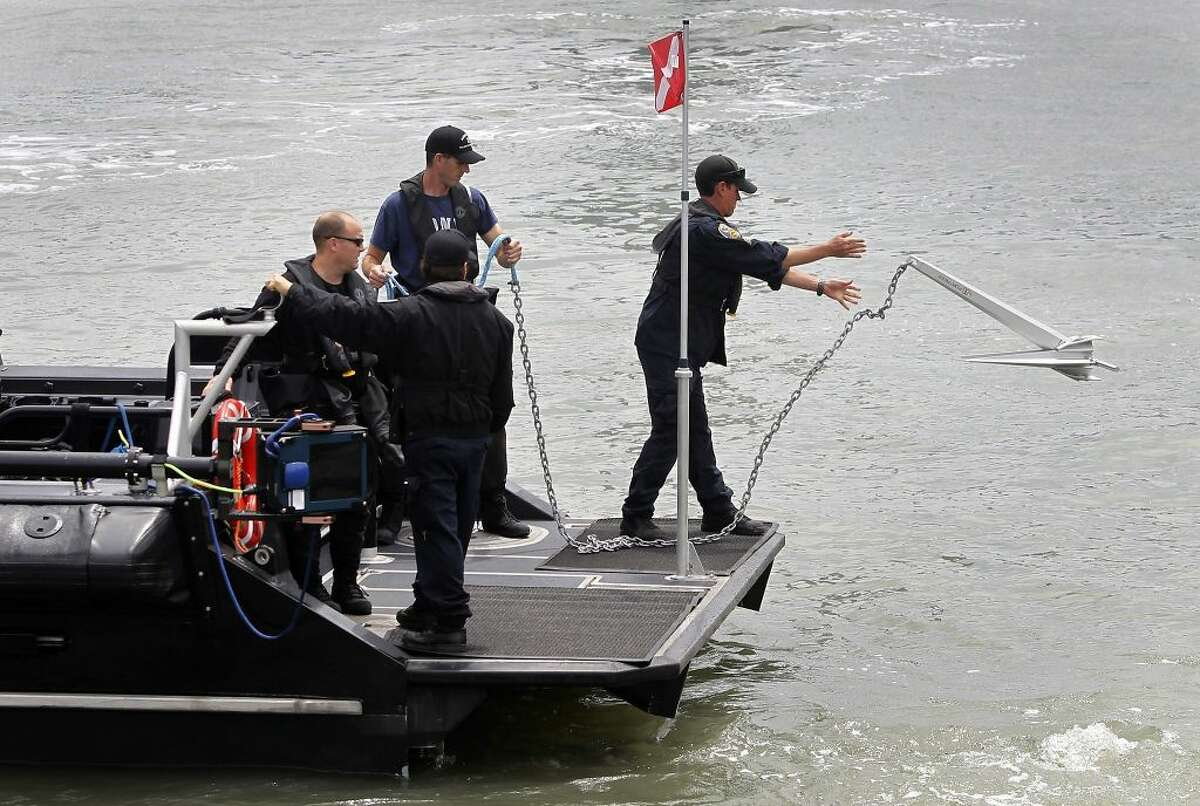 A police department dive team drops anchor before searching for evidence off of Pier 14 in San Francisco, Calif. on Thursday, July 2, 2015 after a woman was shot and killed walking on the pier with her father yesterday afternoon.