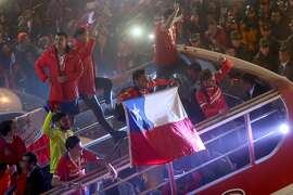 Chile's football team players wave at the crowd from the bus that takes them to La Moneda presidential palace in Santiago, on July 4, 2015 during the celebration upon winning the Copa America 2015. Chile defeated Argentina in a penalty shootout 4-1 (0-0) and won the tournament. AFP PHOTO/FELIPE FREDES FERNANDEZ/AGENCIAUNO    CHILE OUTFELIPE FREDES FERNANDEZ/AFP/Getty Images