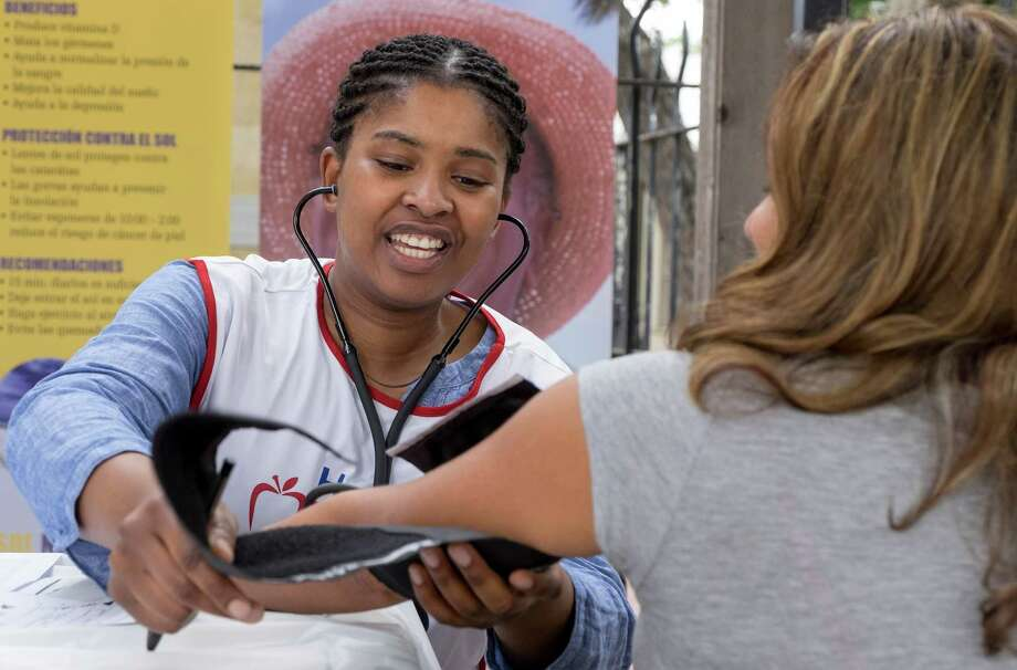 Nomsa Maphango takes Astrid Guerrero's blood pressure during the Seventh-day Adventist Church's InStep for Life Health Expo at La Villita. San Antonians will have three more opportunities for free InStep for Life health screenings this week. Photo: Photos By Darren Abate /For The San Antonio Express-News