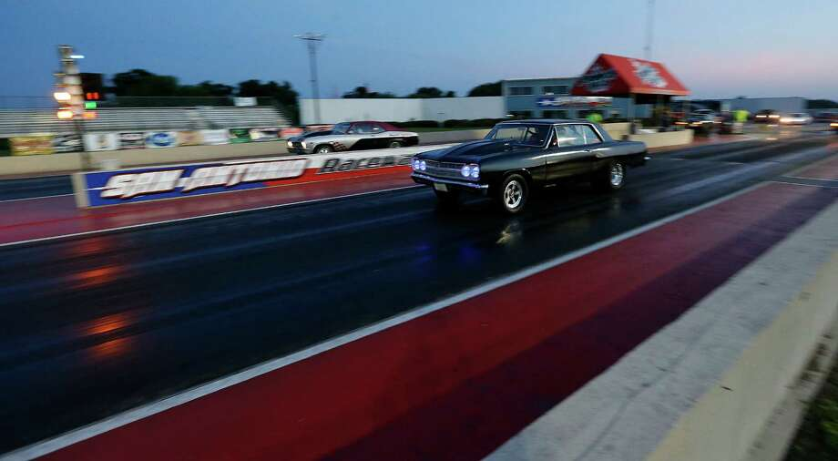 Bobby Baker and his Chevy Chevelle hot rod lurches forward at the starting line to blast down the quarter-mile track at San Antonio Raceway near Marion, Texas on Friday, July 3, 2015. The raceway re-opened after a six-month hiatus with a change of ownership and racers from around the area have come back in numbers. On Friday, nearly 200 racers waited their turn to race at the track located 26 miles East of downtown San Antonio. (Kin Man Hui/San Antonio Express-News) Photo: Kin Man Hui, Staff / San Antonio Express-News / ©2015 San Antonio Express-News