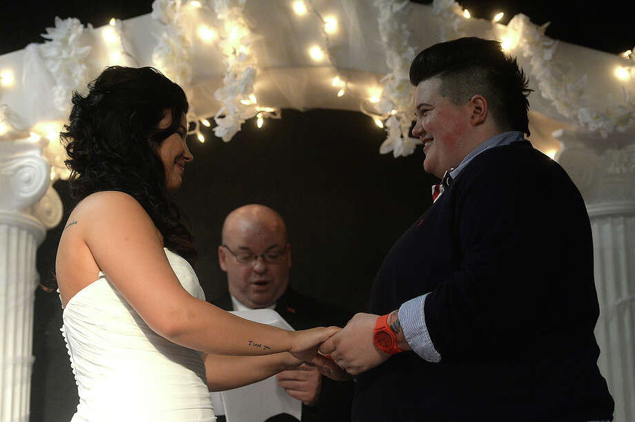 Ashlee Cassity (right) and Taylor Maltba hold hands as ordained officiate David Ball reads a passage from the Bible during their wedding ceremony at FAME in Beaumont Saturday. Photo taken Saturday, July 04, 2015 Kim Brent/The Enterprise Photo: Kim Brent / Beaumont Enterprise