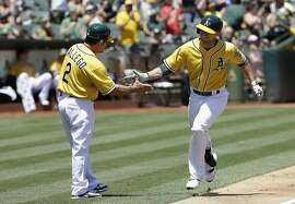 Oakland Athletics' Sam Fuld, right, is congratulated by third base coach Mike Gallego (2) after hitting a solo home run off of Seattle Mariners pitcher Mike Montgomery during the third inning of a baseball game in Oakland, Calif., Sunday, July 5, 2015. (AP Photo/Jeff Chiu)