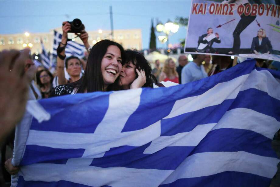 """ATHENS, GREECE - JULY 05:  People celebrate in front of the Greek parliament as early opinion polls predict a win for the Oxi, or No, campaign in the Greek austerity referendum. Crowds are begining to gather in the squares of Athens waiting for the official result on July 5, 2015 in Athens, Greece. The people of Greece went to the polls to decide if the country should accept the terms and conditions of a bailout with its creditors. Greek Prime Minister Alexis Tsipras is urging people to vote """"a proud no"""" to European creditors' proposals, and """"live with dignity in Europe"""". 'Yes' campaigners believe that a no vote would mean financial ruin for Greece and the loss of the Euro currency.  (Photo by Christopher Furlong/Getty Images) *** BESTPIX *** Photo: Christopher Furlong, Staff / 2015 Getty Images"""