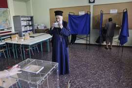 "ATHENS, GREECE - JULY 5:  An Orthodox priest prepares to put a referendum vote in the ballot box at a school on July 5, 2015 in Athens, Greece. The people of Greece are going to the polls to decide if the country should accept the terms and conditions of a bailout with its creditors. Greek Prime Minister Alexis Tsipras is urging people to vote ""a proud no"" to European creditors' proposals, and ""live with dignity in Europe"". 'Yes' campaigners believe that a no vote would mean financial ruin for Greece and the loss of the Euro currency. (Photo by Milos Bicanski/Getty Images) *** BESTPIX ***"