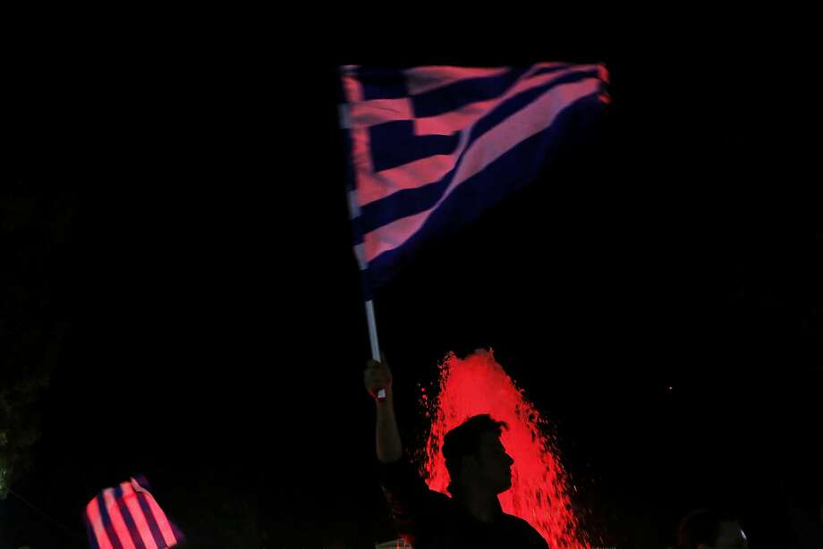 A supporter of the No vote waves a Greek flag as celebrates after the results of the referendum in Synatagma square in central Athens, Sunday, July 5, 2015. Voters in Greece resoundingly rejected creditors' demands for more austerity in return for rescue loans Sunday, backing Prime Minister Alexis Tsipras, who insisted the vote would give him a stronger hand to reach a better deal.  Photo: Petros Karadjias, Associated Press