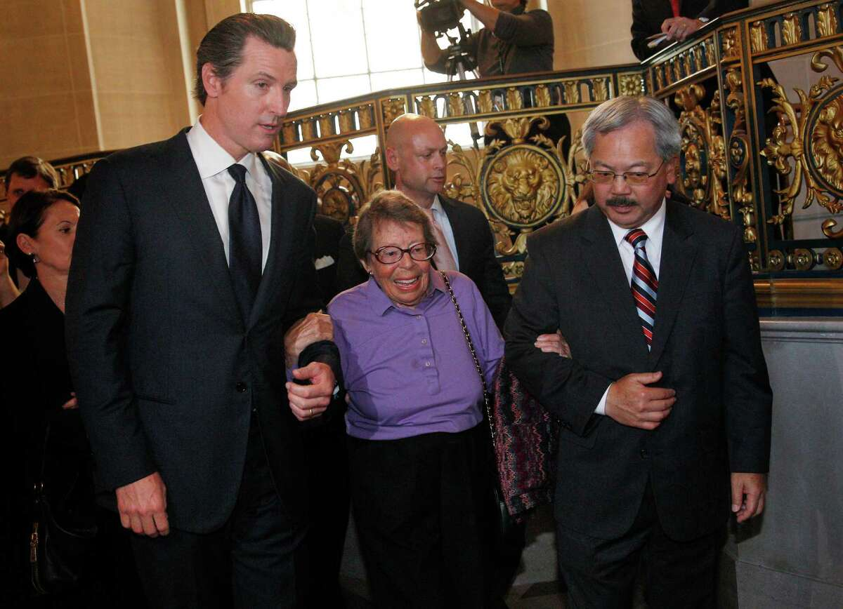 Lieutenant Governor Gavin Newsom (left) and Mayor Ed Lee (right) escort Phyllis Lyon (center) as they prepare to walk down the steps in the rotunda at City Hall for a press conference after the Supreme Court handed down their decisions on Wednesday, June 26, 2013 in San Francisco, Calif. The Supreme Court handed down their decisions dismissing California's Proposition 8 and striking down the Defense of Marriage Act.