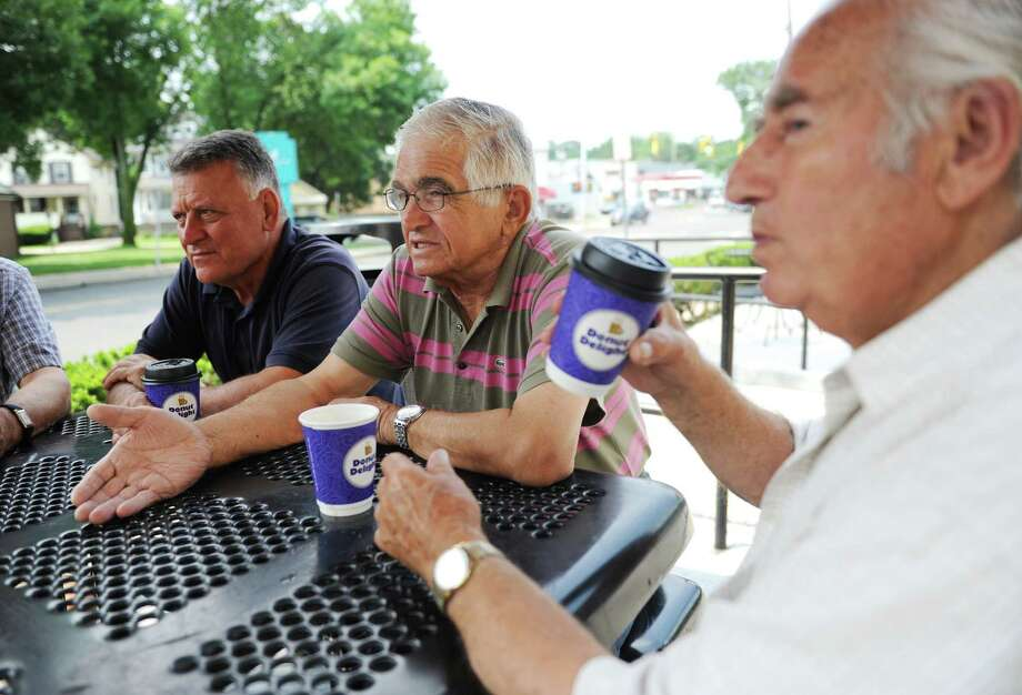 Stamford's Andy Vlogiannitis, left, and Terry Nanos, center, and John Bilas sip coffee and chat at a table outside of Donut Delight in Stamford. The group of retired Greek-American men frequently gather at the donut joint to chat about memories of their time in Greece, speak the language and discuss the state of the country. Photo: Tyler Sizemore / Hearst Connecticut Media / Greenwich Time