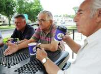 Stamford's Andy Vlogiannitis, left, and Terry Nanos, center, and John Bilas sip coffee and chat at a table outside of Donut Delight in Stamford. The group of retired Greek-American men frequently gather at the donut joint to chat about memories of their time in Greece, speak the language and discuss the state of the country.