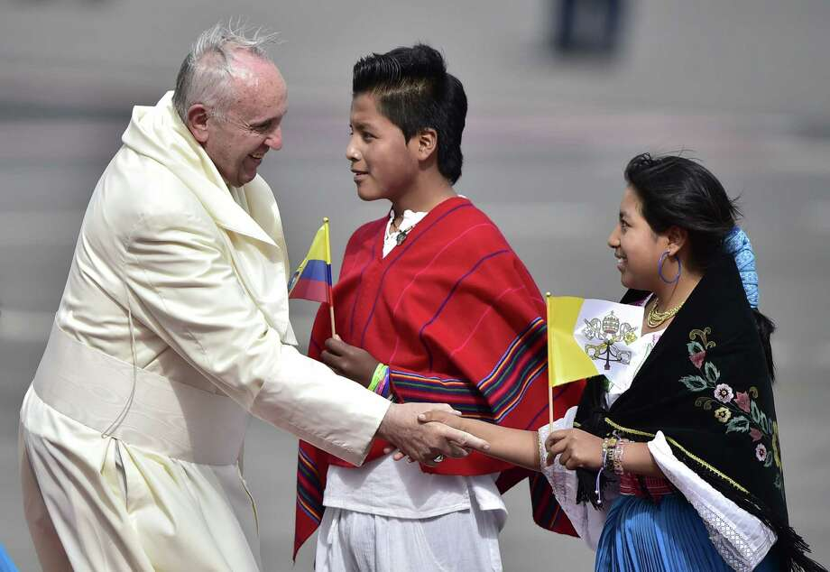 Pope Francis is welcomed by two young faithful upon landing at the Mariscal Sucre international airport Sunday in Quito. Francis' trip will continue to Bolivia on Wednesday and then to Paraguay. Photo: RODRIGO BUENDIA, Staff / AFP