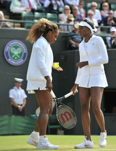 US player Serena Williams (L) and her partner US player Venus Williams (R) warm up for their women's doubles second round match against Germany's Kristina Barrois and Switzerland's Stefanie Voegele on day eight of the 2014 Wimbledon Championships at The All England Tennis Club in Wimbledon, southwest London, on July 1, 2014. US superstar Serena Williams was at the centre of a Wimbledon health scare when she wept and appeared to be close to fainting in a doubles match with sister Venus. Serena, the world number one singles player, called the doctor to Court One just after she and Venus had warmed up for their second round match against Kristina Barrois and Stephanie Voegele. She broke down in tears as she consulted with the doctor and physio before the tournament referee and supervisor were called to court in a reflection of her status in the sport. The Williams sisters retired from the match.  AFP PHOTO / GLYN KIRK  - RESTRICTED TO EDITORIAL USE        (Photo credit should read GLYN KIRK/AFP/Getty Images) Photo: GLYN KIRK, Stringer / AFP