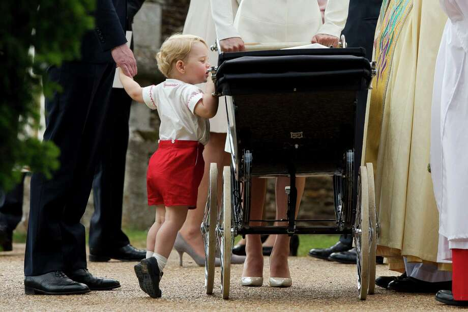 Prince George gets up on tiptoes to peek into the pram of his sister, Princess Charlotte. Photo: Matt Dunham, STF / AP POOL