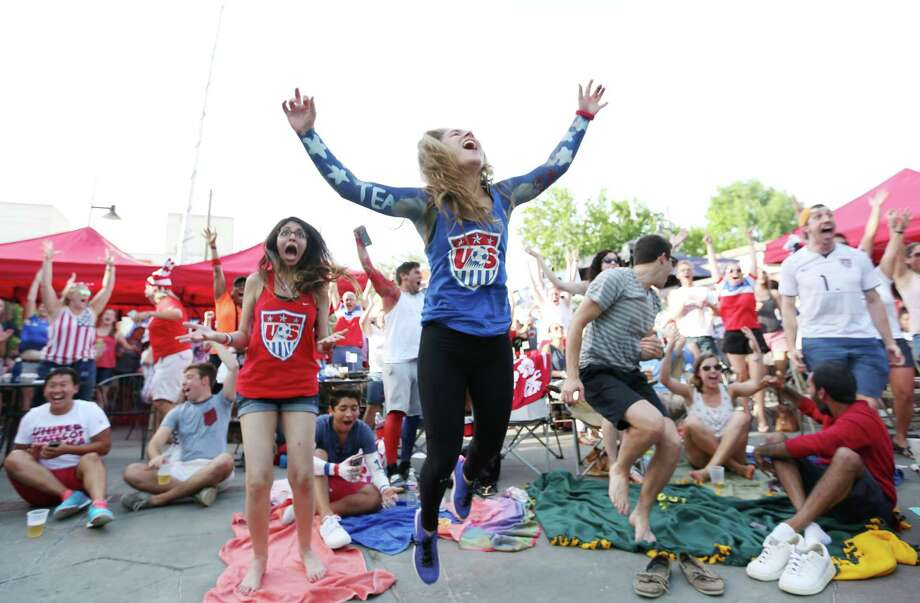 Seleya Tanner, from Houston, in blue, and Ragini Mahajan, celebrate a US goal at a watch party for Women's World Cup Final at the Phoenix on Westheimer Sunday, July 5, 2015, in Houston. Tanner became interested in the team because of the hype around it. Photo: Jon Shapley, Houston Chronicle / © 2015 Houston Chronicle