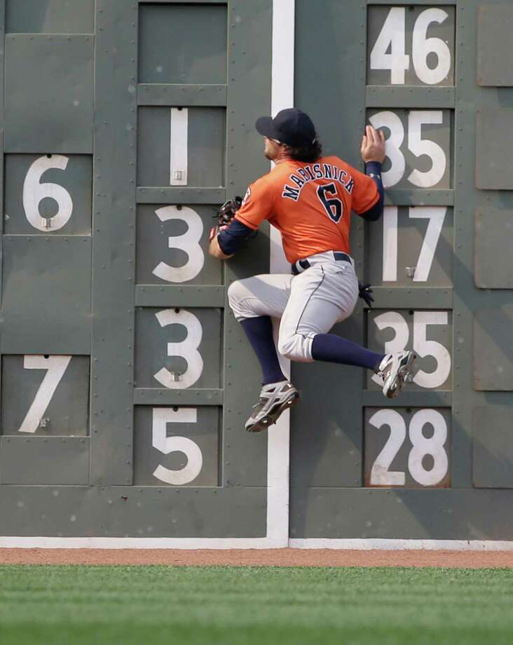 Astros center fielder Jake Marisnick crashes into the scoreboard on the Green Monster to take a hit away from the Red Sox's Brock Holt to end the sixth inning. Photo: Steven Senne, STF / AP