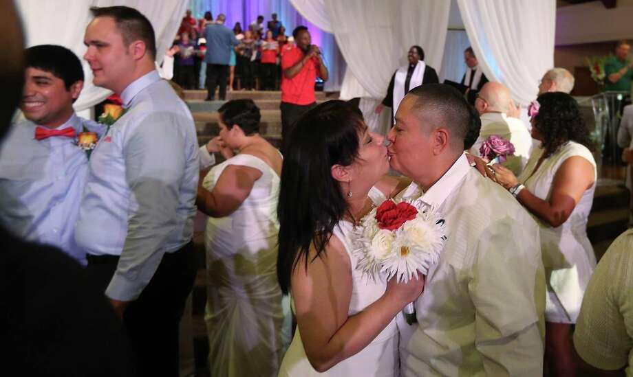 Newlyweds Tina Renteria-Flores and Norma Flores celebrate their union Sunday at Resurrection Metropolitan Community Church.  Photo: Mayra Beltran, Staff / © 2015 Houston Chronicle
