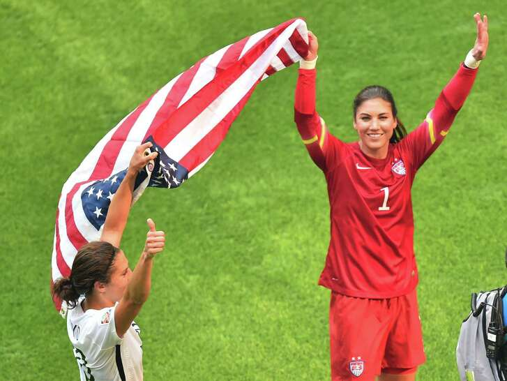 The USA's goalkeeper Hope Solo (R) and Carli Lloyd  celebrate, holding the US national flag, after defeating Japan in the 2015 FIFA Women's World Cup final at BC Place Stadium in Vancouver, British Columbia on July 5, 2015.   AFP PHOTO/NICHOLAS KAMMNICHOLAS KAMM/AFP/Getty Images