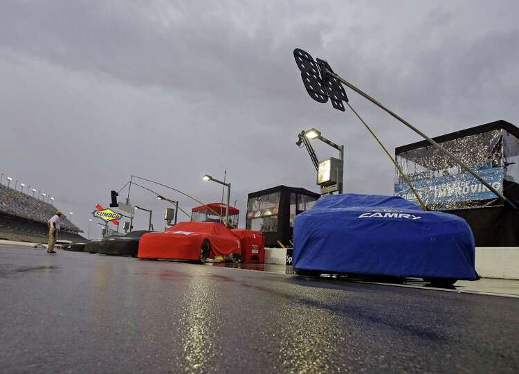 Cars under rain covers line up on pit road during a weather delay before the start of a NASCAR Sprin