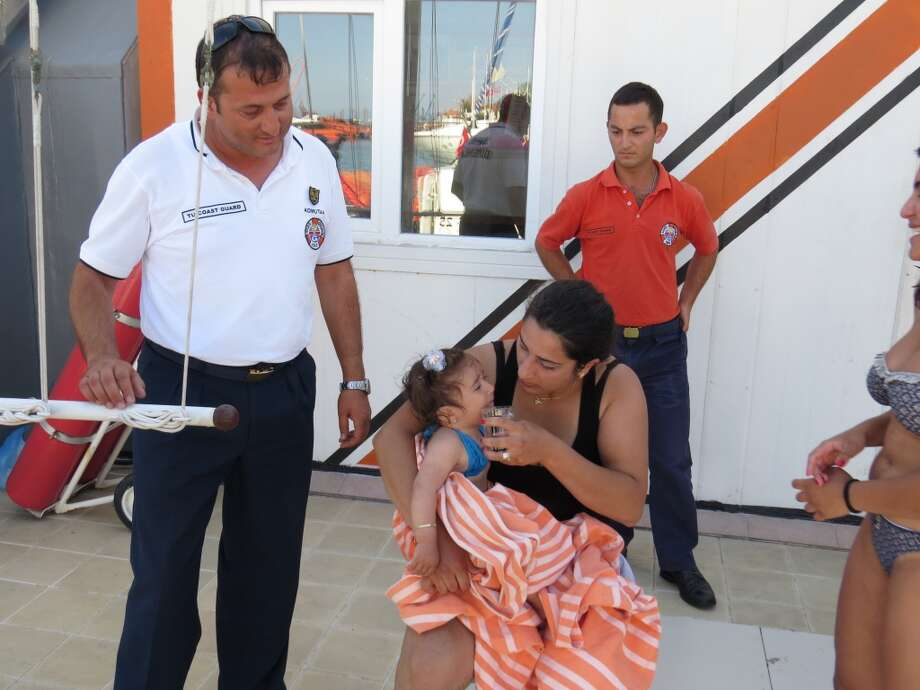 Ten-month-old baby Melda Ilgin is seen on her mother's lap after being saved by Turkish coast guard when she drifted a kilometer out to sea on a sea buoy in Ayvacik district of Canakkale province, Turkey on July 3, 2015. Photo: Anadolu Agency, Getty