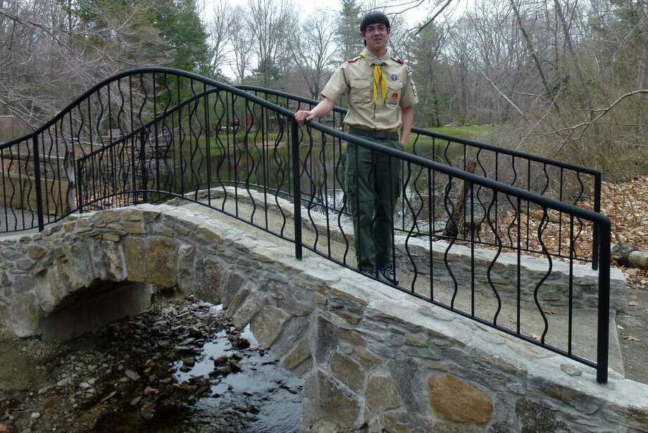 Boy Scout Gabriel Bay of Troop 90 with the arched stone bridge he designed, and with help from fellow Scouts, built as his Eagle Scout project in the Connecticut Audubon Society's Larsen Sanctuary. Photo: Contributed / Contributed Photo / Fairfield Citizen