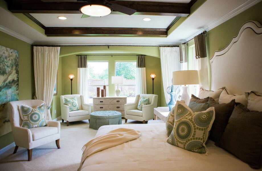 The master bedroom is designed to be a retreat and a workspace, with solid wood desks serving as nightstands on each side of the bed. Custom bedding was made by Heine's Custom Draperies in Katy. Photo: Marie D. De Jesus, Staff / © 2015 Houston Chronicle