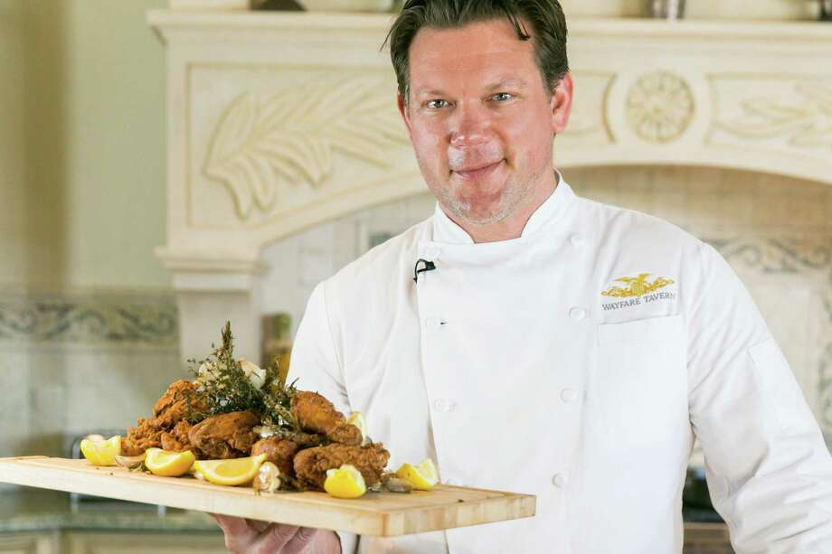 Tyler Florence displays fried chicken complete with fried herbs, garlic and lemon wedges.  Photo: Tina Case, Freelance / ONLINE_YES
