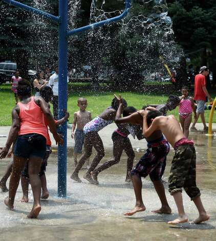 A group of campers from Pastor Charlie's Hip Hop Hope Camp enjoy the cooling waters of the Swinburne Park Spray Pool Monday afternoon, July 6, 2015, in Albany, N.Y. Tthe Hip Hop Hope Camp will run daily through the end of August and is free for children ages 5-12.  There are several locations where Pastor Charlie's Trolly pick up the children and transport them to Swinburne Park in Albany.    (Skip Dickstein/Times Union) Photo: SKIP DICKSTEIN