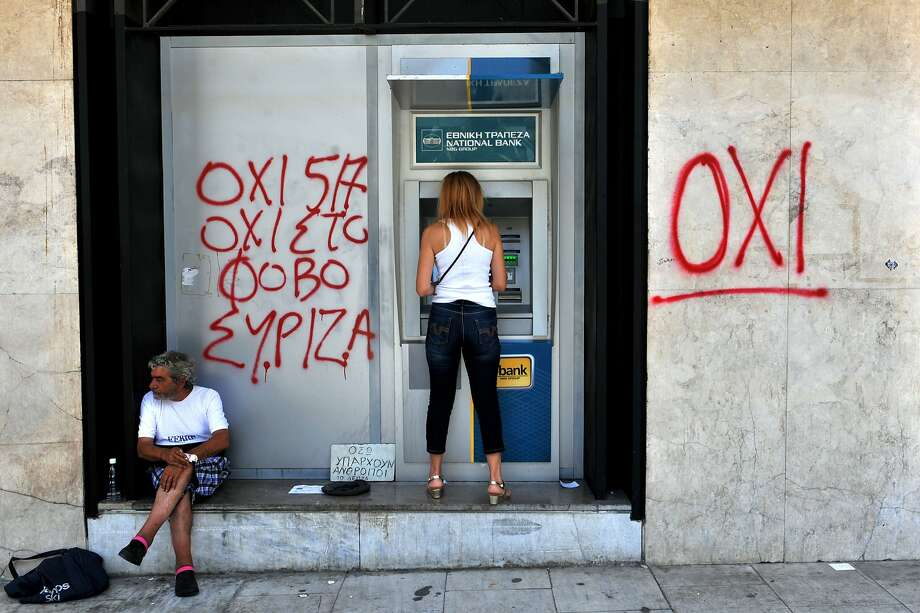 """A woman withdraws money from an ATM next to graffiti reading """"No to fear"""" in Thessaloniki Monday. Photo: Sakis Mitrolidis, AFP / Getty Images"""