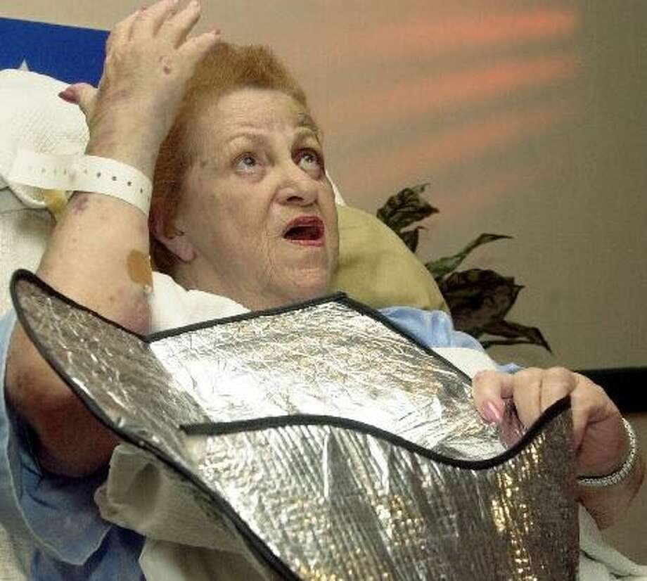 August 18, 2000: At a hospital news conference, Tillie Tooter re-enacts how, while trapped for three days in a snake-infested swamp, she collected rainwater in her steering-wheel cover. Photo: MARTA LAVANDIER, AP