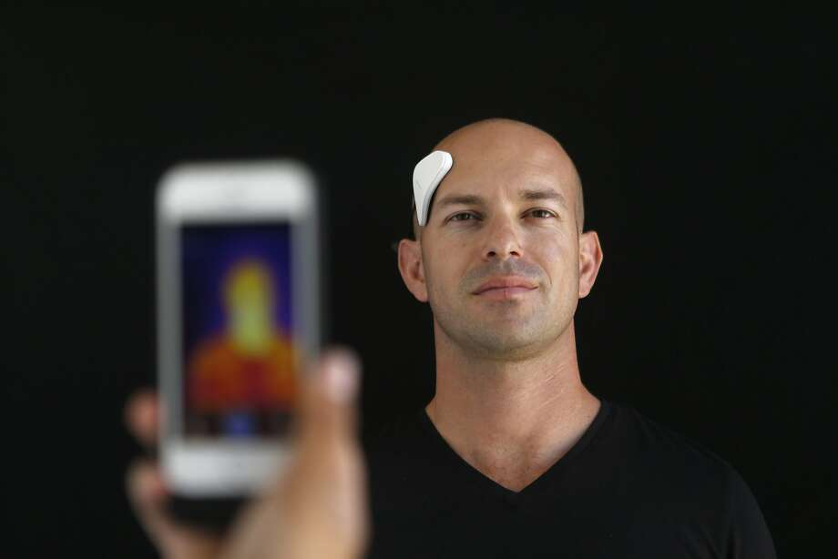 Dan Wetmore demonstrates the Thync, a bluetooth connected wearable device that sends electronic pulses to your cranial nerves to either make your calmer or more energized, depending on your preference, at Thync in Los Gatos, Calif., on June 1, 2015. Infrared photography can show how the device heats up areas of the face and neck. (Jim Gensheimer/Bay Area News Group/TNS) Photo: Jim Gensheimer, McClatchy-Tribune News Service