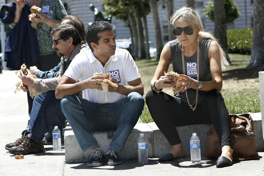 """Timur Kahn (left) and Agnieszka Pilat (right) representing in a new group called """"San Francisco for Everyone"""" have lunch next to city hall steps after rallying in San Francisco, Calif., on Monday, July 6, 2015. They rallied to protest the expected filing of signatures for a November ballot initiative that would clamp down on home sharing in private homes. Kahn shares a studio he lives in. Photo: Liz Hafalia, The Chronicle"""