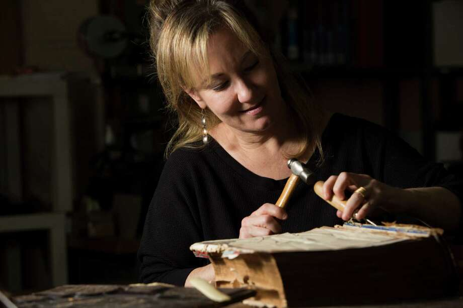 Deborah Karchmer, owner of Bella Becho Book & Print Bindery, removes the original spine of a 1800s Bible for restoration purposes last month in Houston. Photo: Marie D. De Jesus, Houston Chronicle / © 2015 Houston Chronicle
