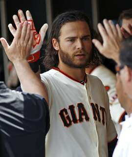 San Francisco Giants' Brandon Crawford is greeted in the dugout after hitting a home run against the  Colorado Rockies during the sixth inning of a baseball game, Sunday, June 28, 2015, in San Francisco. (AP Photo/George Nikitin)