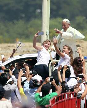 Two women climb onto crowd barriers to take selfies with Pope Francis as he waves to the crowd Monday in Parque de Semanes in Guayaquil, Ecuador, before he delivers the first Mass of his trip to Latin America. Photo: Fernando Vergara, STF / AP