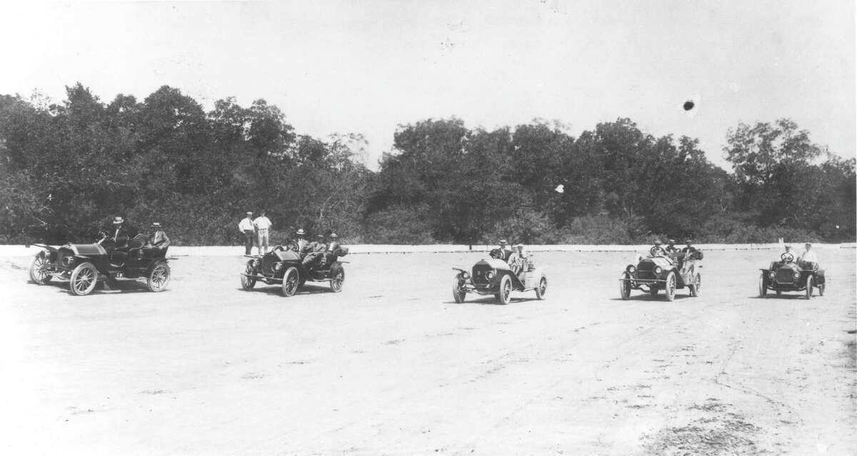 """This photo, circa 1906, shows a group of vehicles lined up for a """"Sunday morning meet."""" The location in Bexar County is not known but experts state that Atlee B. Ayers and his sons, Robert and Atlee, are in the third car from the left. Although the photo seems to indicate they are on some type of race track, that cannot be verified."""