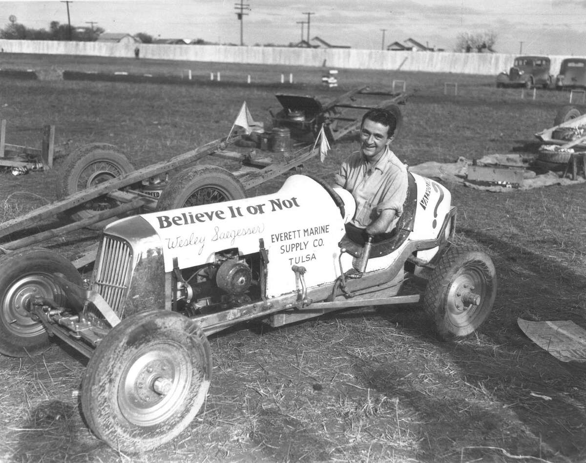 """One of the most popular drivers in Texas in the 1930s was Wesley Saegesser, who was known as the """"one armed driver."""" Saegesser is shown here in a midget race car before a local race in February 1938. Note the race car trailers and fuel cars nearby."""