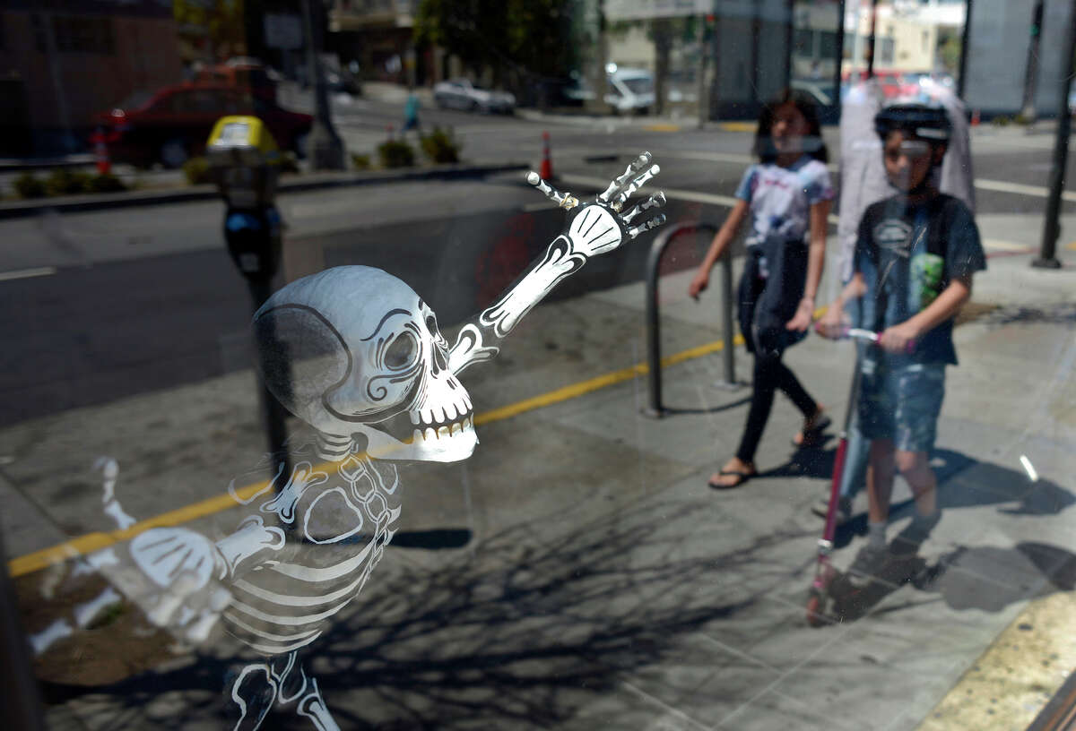 A skeleton greets passers-by in the window of La Urbana, a restaurant on changing Divisadero Street.