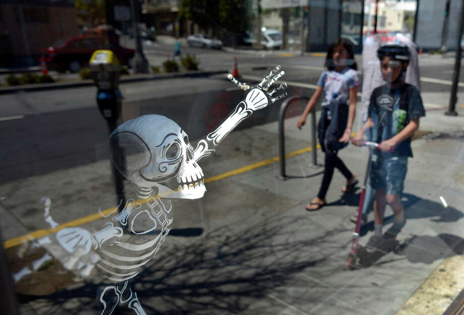 A skeleton greets passers-by in the window of La Urbana, a restaurant on changing Divisadero Street. Photo: Brandon Chew / Photos By Brandon Chew / The Chronicle / ONLINE_YES