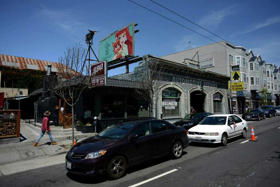 A BBQ restaurant sits next to an automotive service center with a pet adoption ad above it on Divisadero Street in San Francisco, California, on Tuesday, June 30, 2015. Photo: Brandon Chew / The Chronicle / ONLINE_YES