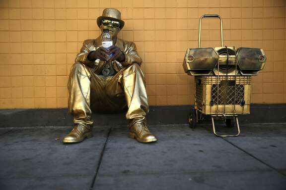 Street performer Ronnie Darden waits on Powell Street for a bus after a day of entertaining at Fisherman's Wharf in San Francisco, Calif., on Monday, July 6, 2015.