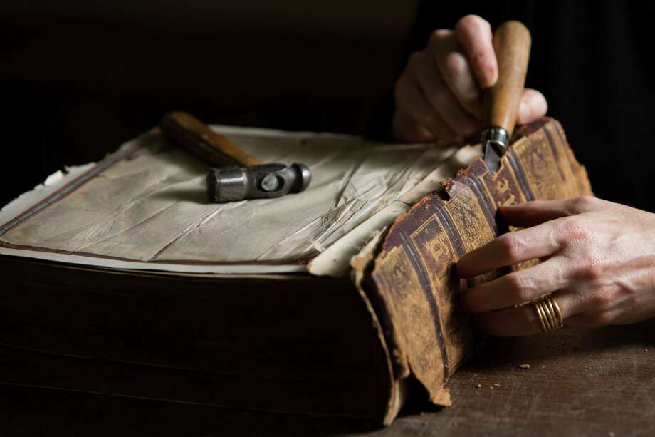 Deborah Karchmer owner of Bella Becho Book & Print Bindery removes the original spine of a 1800s Bible for restoration purposes. Thursday, June 18, 2015, in Houston. ( Marie D. De Jesus / Houston Chronicle ) Photo: Marie D. De Jesus, Staff / © 2015 Houston Chronicle