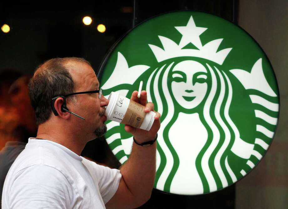FILE - In this July 11, 2013  file photo, a man drinks a Starbucks coffee in New York. Starbucks says it's hiking prices again starting Tuesday, July 7, 2015, with the increases ranging from 5 to 20 cents for most affected drinks. (AP Photo/Mark Lennihan, File) Photo: Mark Lennihan, STF / AP