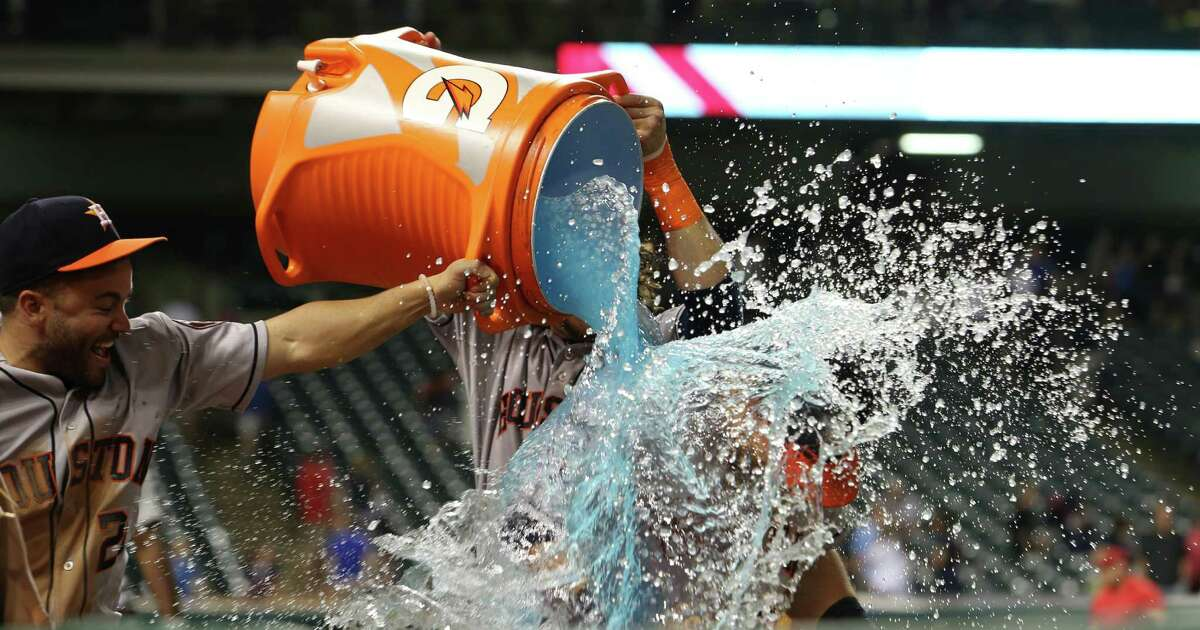 Colby Rasmus gives fellow Astros outfielder Preston Tucker a shower after Tucker's four-hit game Monday night.