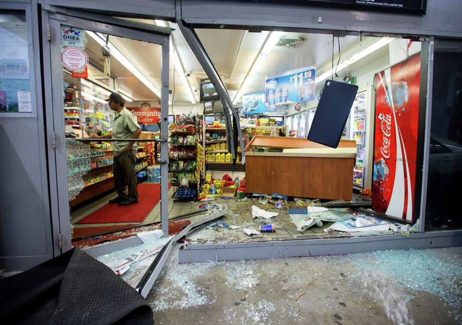 A man makes a purchase from a convenience store after a smash and grab along Gesner near the Westpark Tollway, Monday, July 6, 2015, in Houston. Photo: Cody Duty, Houston Chronicle / © 2015 Houston Chronicle