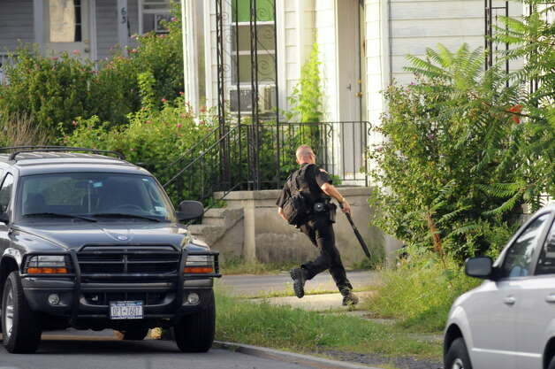 Saratoga County Sheriff officer gets into position on Grace Street as he prepares to evacuate neighbors during a standoff on Monday, Sept. 1, 2014, Waterford, N.Y. (Cindy Schultz / Times Union archive) Photo: Cindy Schultz